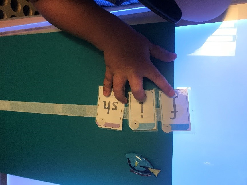 Photo of Sienna at school working with letter cards. Sienna is using a light panel.